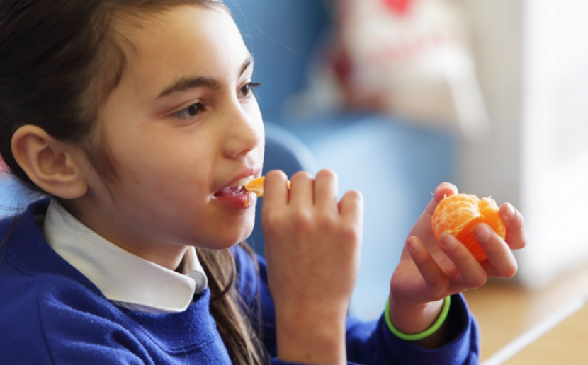 A student eating an orange.