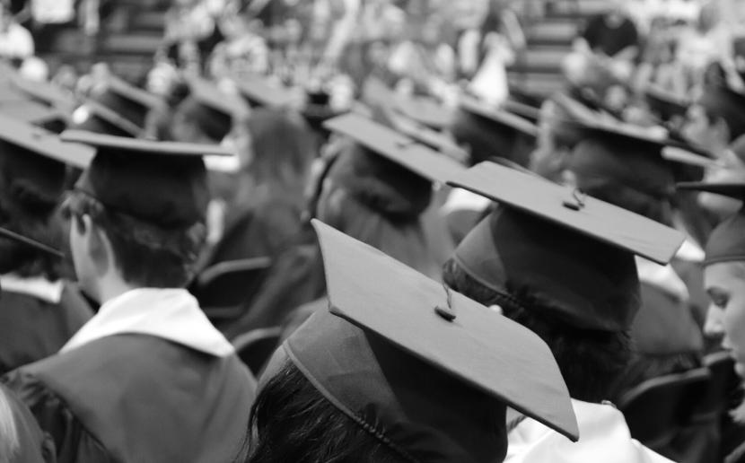 Graduates sit in graduation regalia during ceremony.