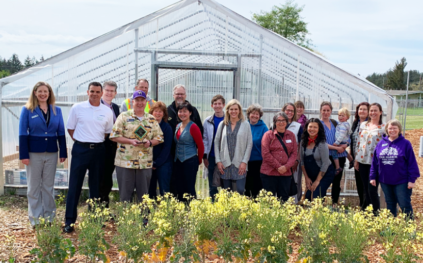 Oak Harbor Public Schools' Green Team pose in front of their greenhouse.