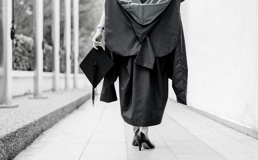 Woman walking down hallway, wearing graduation gown