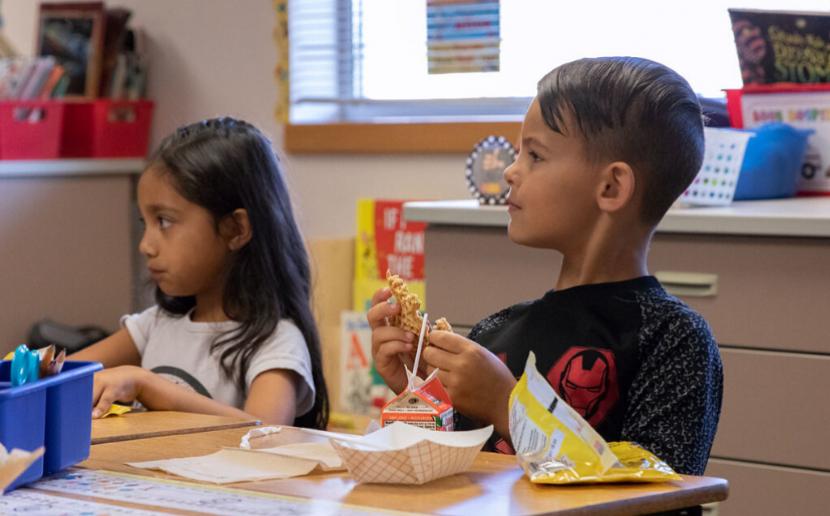 Two students eat breakfast.