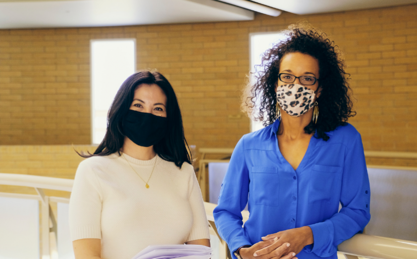 Two teachers wearing masks look at camera